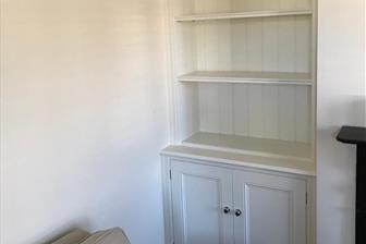 Display bookcases fitted into alcoves either side of the fire